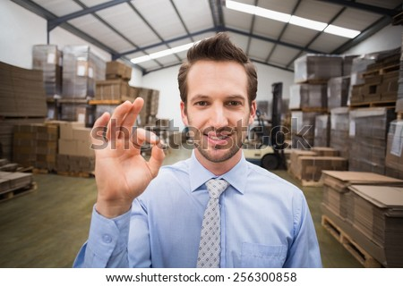 Happy warehouse manager making okay gesture in a large warehouse - stock photo