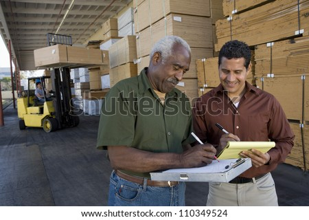 Happy warehouse workers writing on clipboards - stock photo
