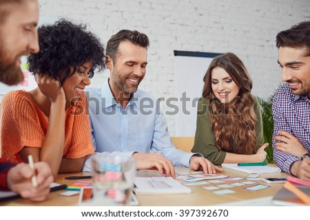 Happy web designers developing new web site layout in the office - stock photo
