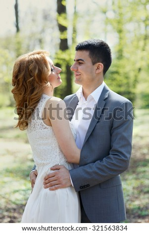 happy wedding couple, elegant bride and handsome groom standing and hugging in sunlit park
