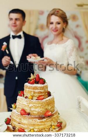 Happy wedding couple handsome groom and blonde bride eating delicious wedding cake - stock photo