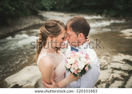 Happy wedding couple hugging and smiling each other on the background lake, forest