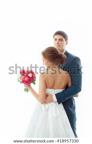 Happy wedding couple in love. Beautiful bride in white dress with brides bouquet and handsome groom in blue suit standing and embracing each other and looking to the camera indoors at home against big - stock photo