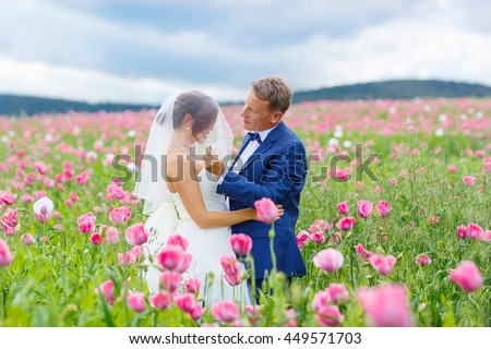 stock photo happy wedding couple in pink poppy field beautiful bride in white dress and groom kissing and 449571703