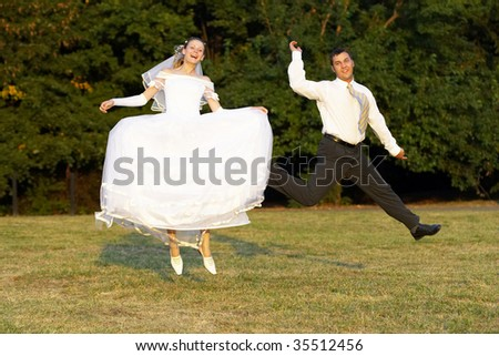 Happy wedding couple jumping in the summer park