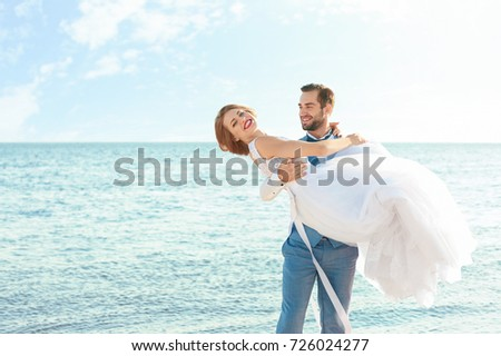 Happy wedding couple on sea beach