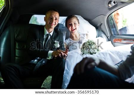 happy wedding couple sitting in limo - stock photo