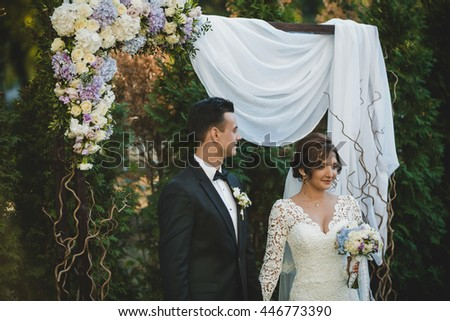 Happy wedding couple stand under a gorgeous wedding altar made of white cloth and wood