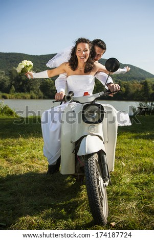 Happy wedding couple take a ride in a white motorcycle. - stock photo