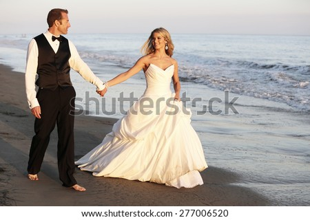 Happy wedding couple walking on the beach - stock photo