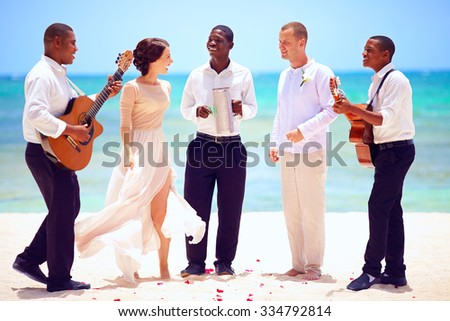 happy wedding couple with musicians dancing on tropical beach