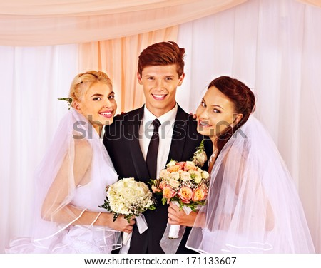 Happy wedding man and two bride holding flower bouquet.