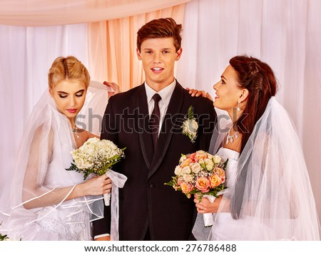 Happy wedding man and two bride holding flower bouquet. Three people.
