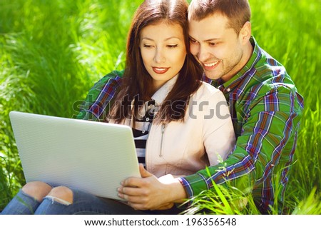 Happy weekend concept. Portrait of a hipster couple in trendy casual clothing sitting in green grass in park, using a laptop and looking happy together. Sunny spring (autumn) weather - stock photo