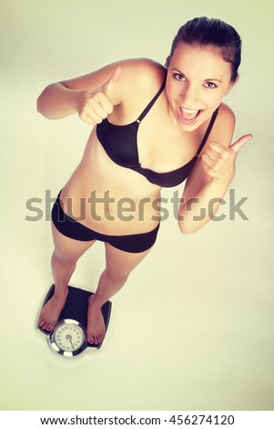 Happy weight loss woman on scale - stock photo
