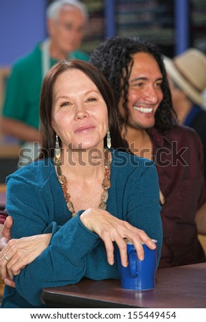 Happy white and Mexican couple sitting in cafe - stock photo