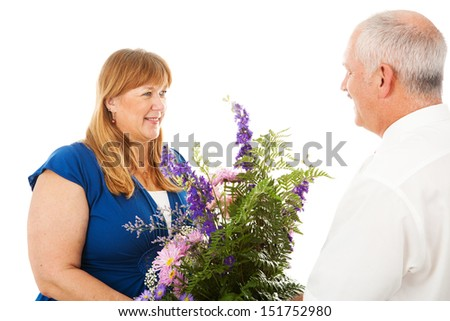 Happy wife receives flowers from her devoted husband.  Isolated on white. - stock photo