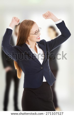 Happy winner businesswoman with hands up.