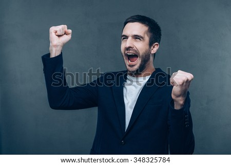 Happy winner. Happy young man gesturing and keeping his mouth open while standing against grey background - stock photo