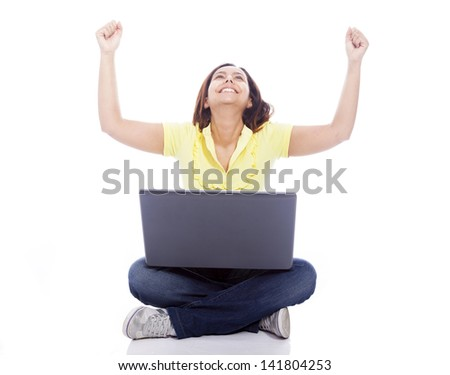 Happy winner woman with arms raised, sitting on the floor with a laptop