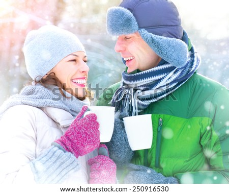 Happy Winter Couple drinking hot beverage outdoors. Having Fun in winter park. Snow. Winter Vacation. Hot Drink Outdoor. Joyful family. St. Valentine's Day celebration - stock photo