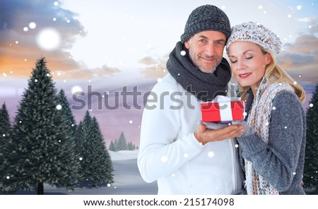 Happy winter couple with gift against snowy landscape with fir trees