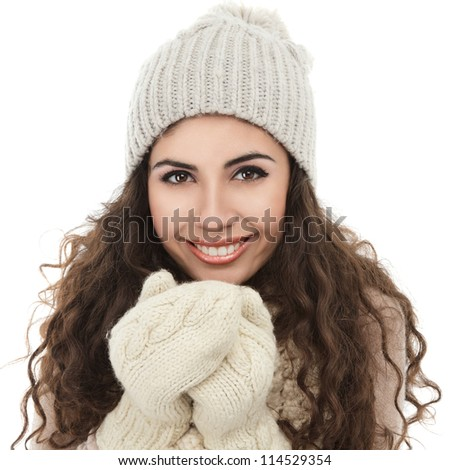Happy winter girl with long curly hair in sweater hat and gloves isolated on white background