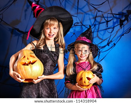 Happy witch children at Halloween party.