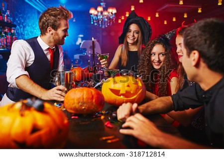 Happy witches celebrating Halloween in bar - stock photo