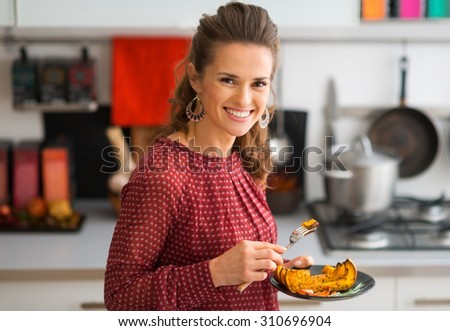 Happy with her delicious roasted pumpkin, an elegant woman smiles at the camera, forked poised. Ah, Thanksgiving... - stock photo