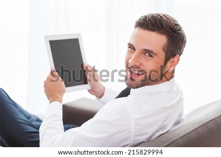 Happy with his new gadget. Rear view of confident young businessman in shirt and tie holding digital tablet and smiling while sitting at the chair - stock photo