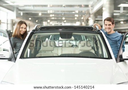 Happy with their new car. Happy young couple standing at both sides of the car smiling at camera - stock photo
