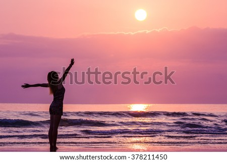 Happy woman admiring beautiful sunrise at the beach - stock photo