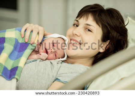 happy woman after birth with a newborn baby