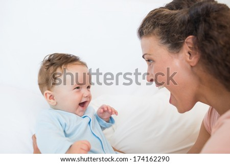 Happy woman and baby boy in bed