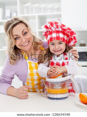 Happy woman and child making fresh orange juice in the kitchen - stock photo