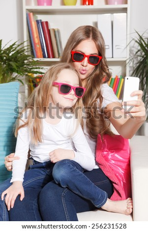 Happy woman and child taking a selfie - stock photo