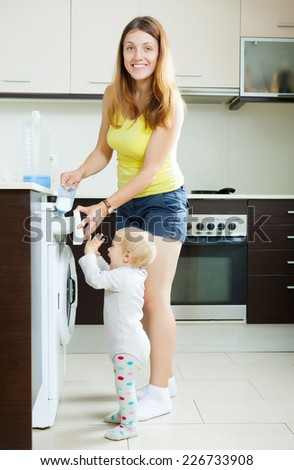 Happy woman and child using washing machine with laundry detergent at home - stock photo