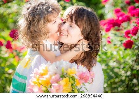 Happy woman and child with beautiful spring flowers against green background. Family holiday concept. Mothers day - stock photo