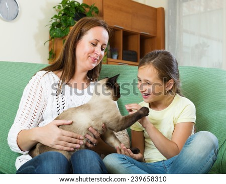 Happy woman and  daughter sitting with cat at home - stock photo