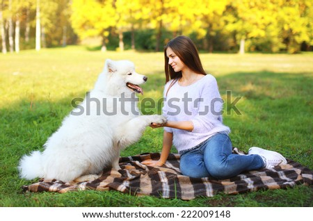 Happy woman and dog resting on the plaid in sunny park, good warm day