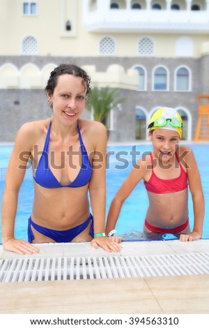 Happy woman and girl in swimsuits in the swimming pool of the hotel - stock photo