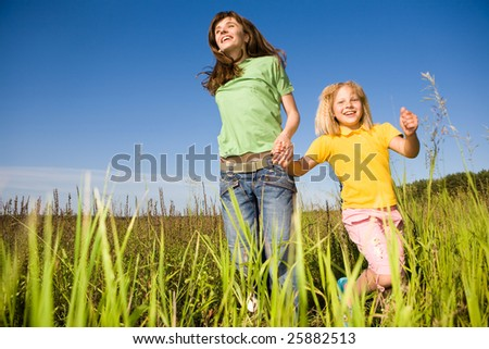 Happy woman and girl making exercises on field - stock photo