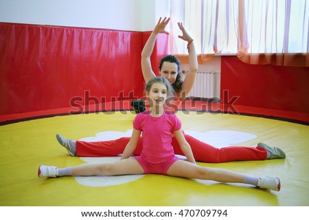 Happy woman and her daughter do exercises in gym with red walls
