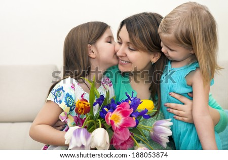 Happy woman and her little daughters in the living room. Mother day concept - stock photo