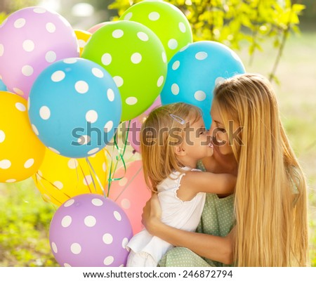 Happy woman and her little daughters with ballons outdoors. Mother day or Birthday concept - stock photo