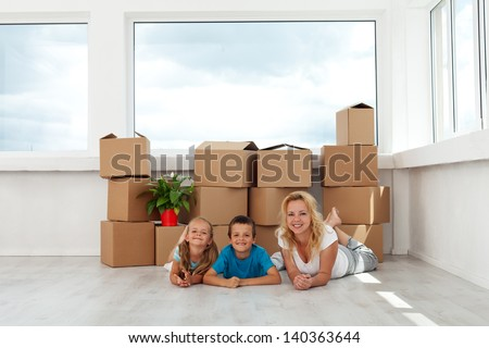Happy woman and kids in their new home - relaxing in front of large window - stock photo