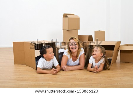 Happy woman and kids relaxing in their new home - moving in with cardboard boxes