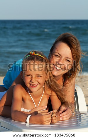 Happy woman and little girl at the sea - relaxing and laughing together - stock photo
