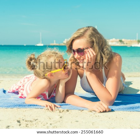 Happy woman and little girl on the beach. - stock photo